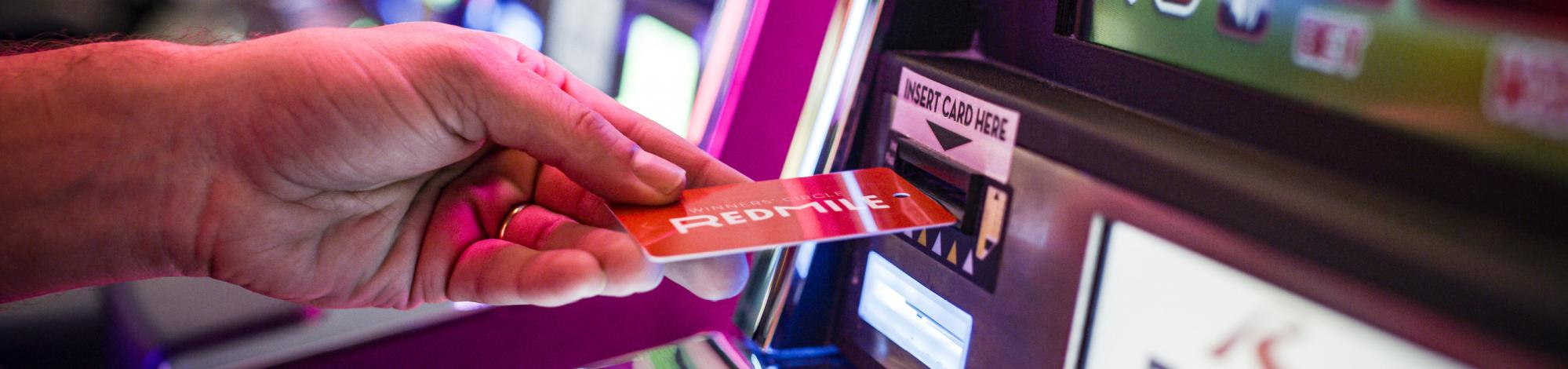 Player inserting Red Mile Circle card into slot machine